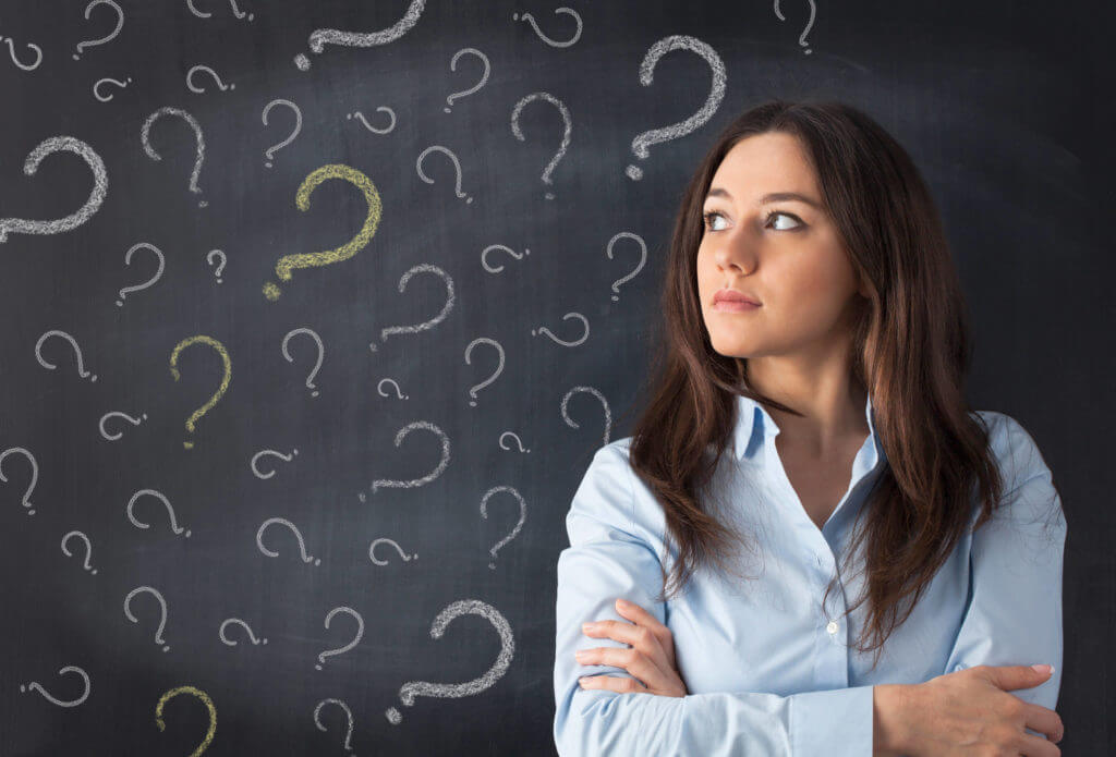 office worker against blackboard filled with question marks