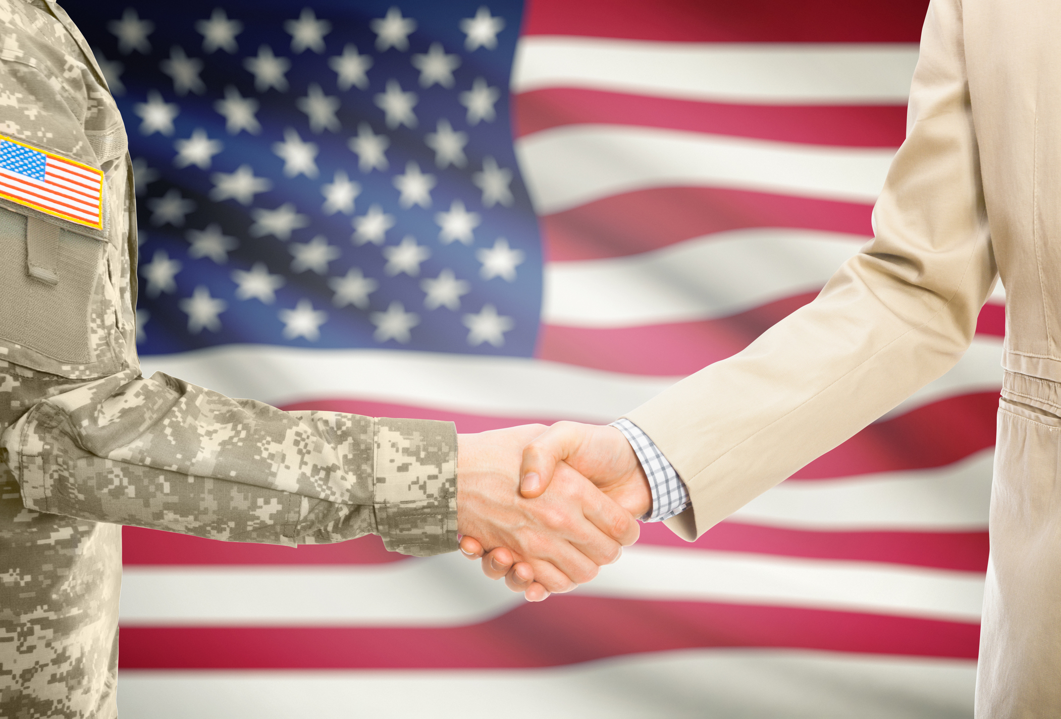 serviceperson shaking hands in front of U.S. flag