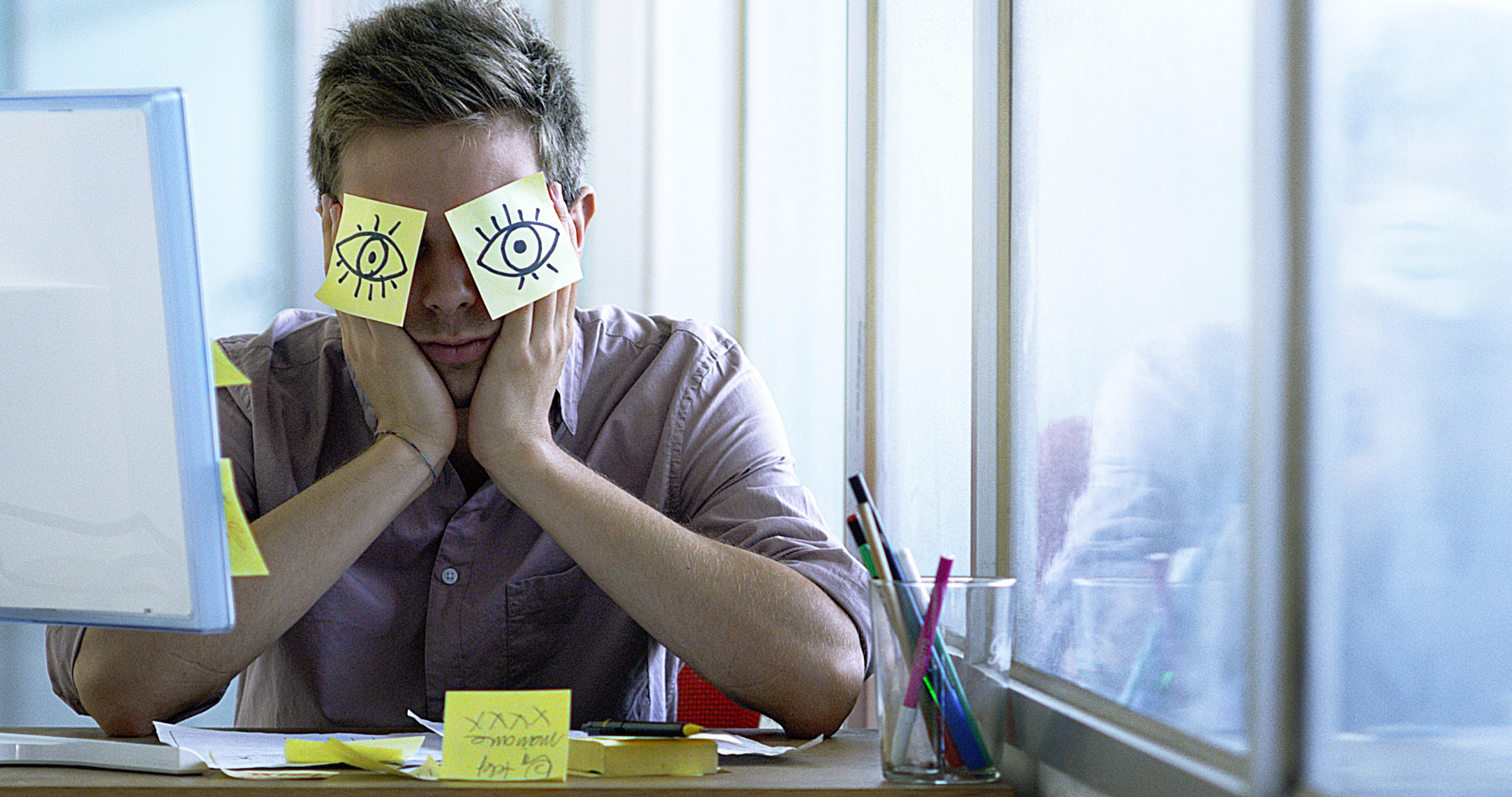 worker resting with post its with hand drawn eyes over face