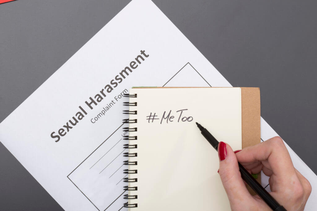 writing #MeToo in notebook on sexual harassment complaint form