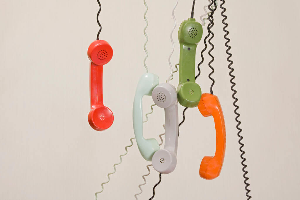 phone handsets hanging by chords