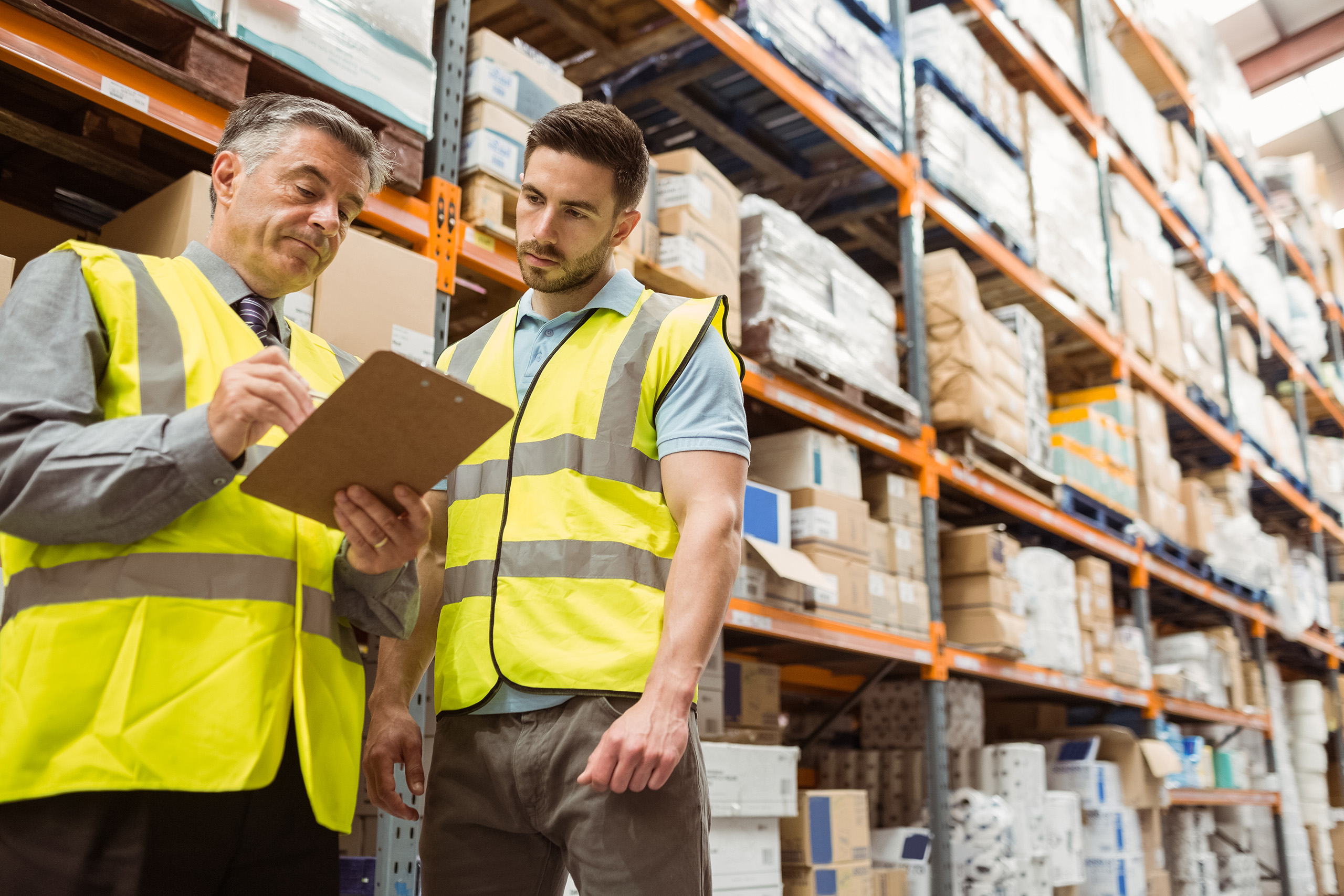 warehouse workers consulting clipboard