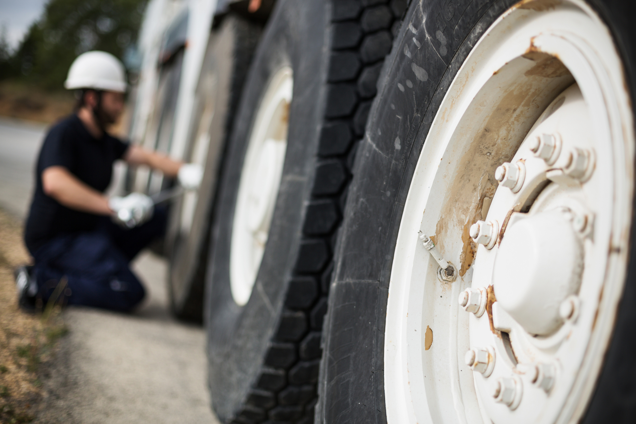 Close-up of truck tire with mechanic on the background
