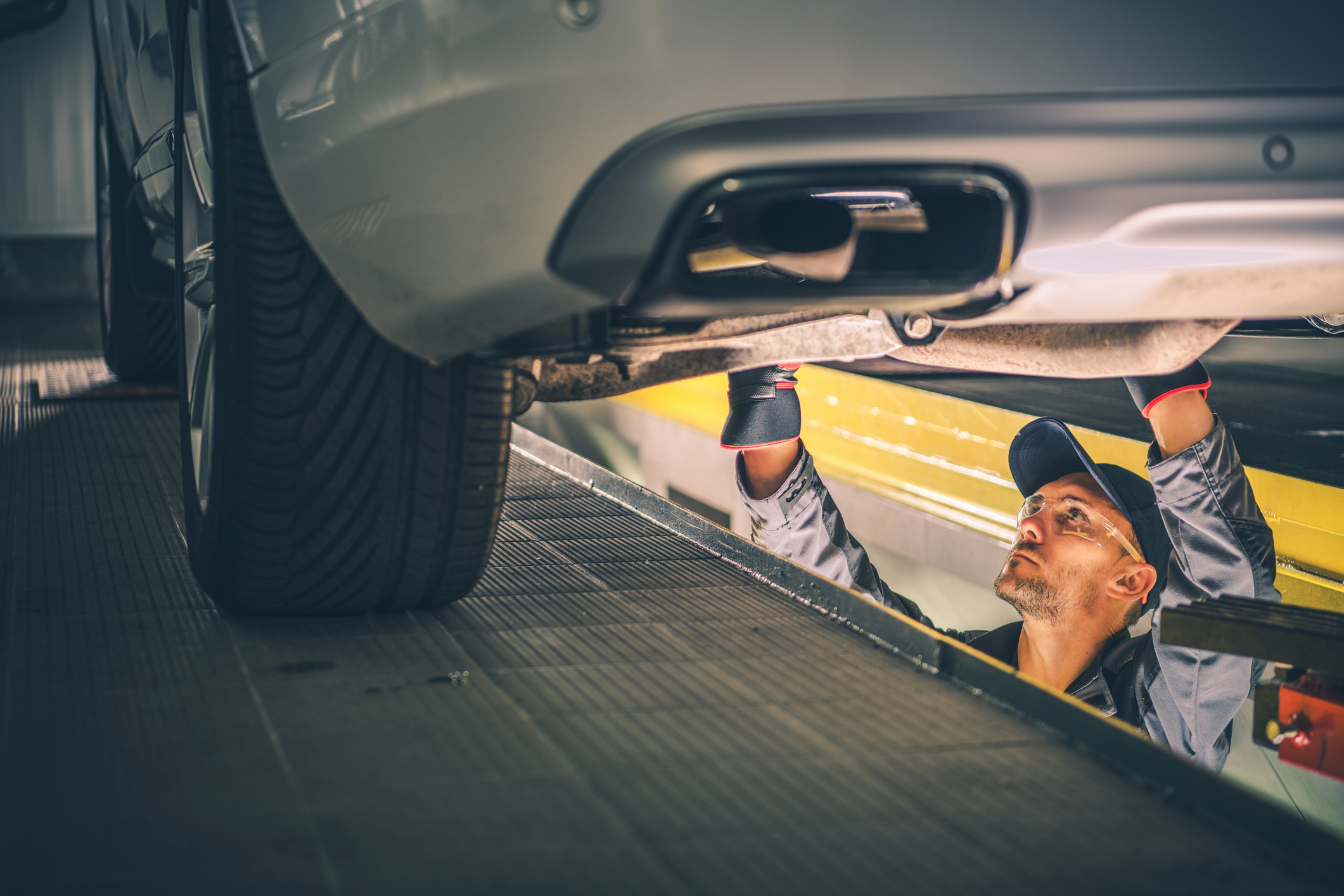 man inspecting standing and inspecting the undercarriage of car in a service dock
