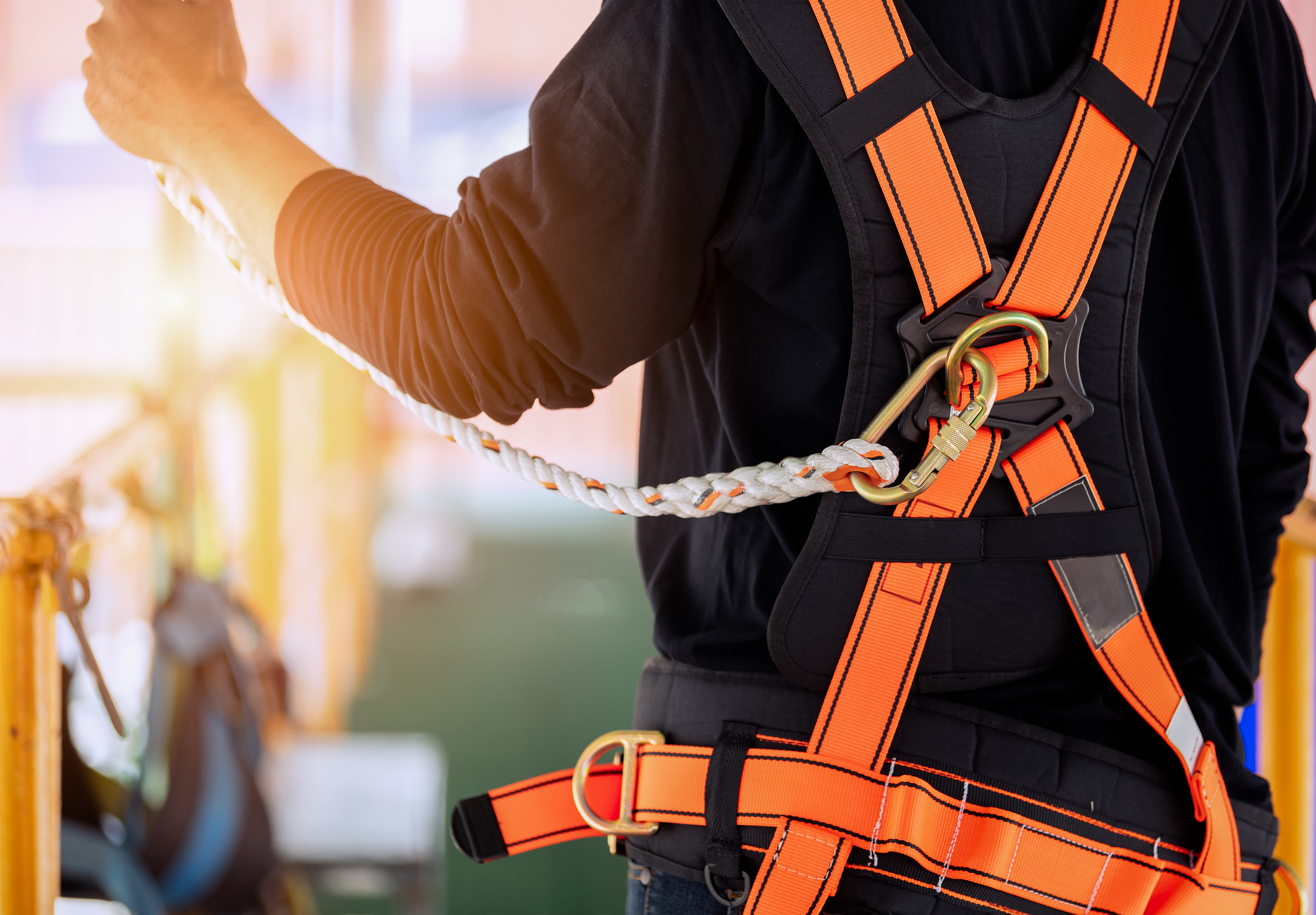 Construction worker wearing safety harness.