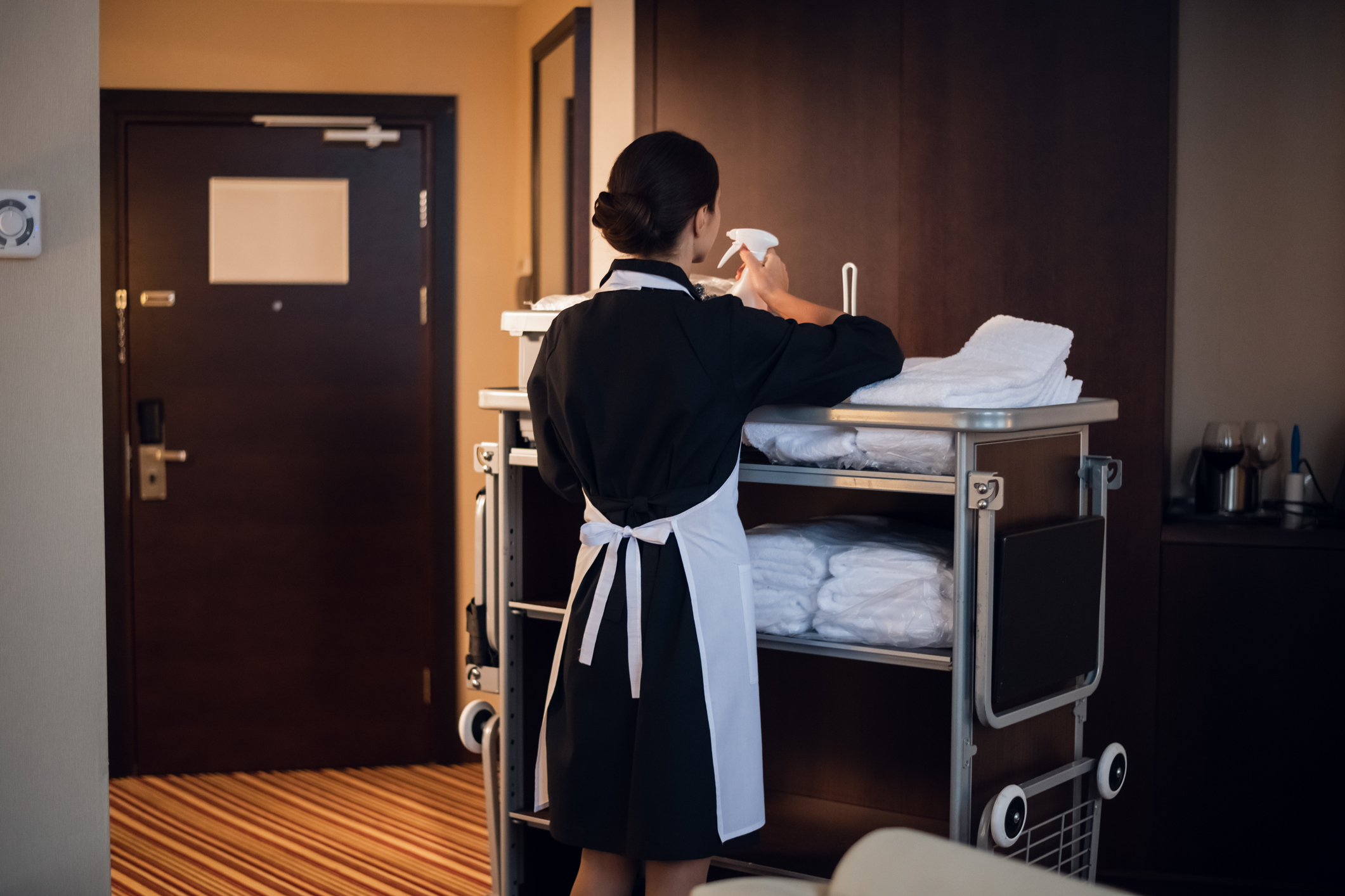 Hotel maid working with cleaning cart and cleaning supplies