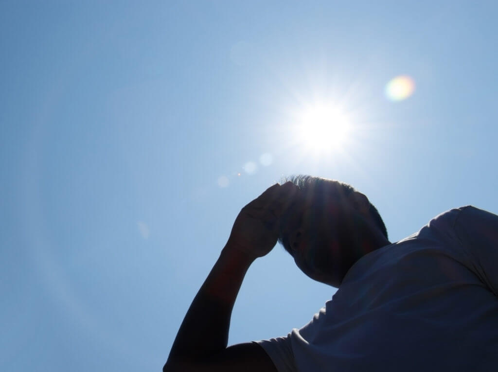 person with hot sun in background