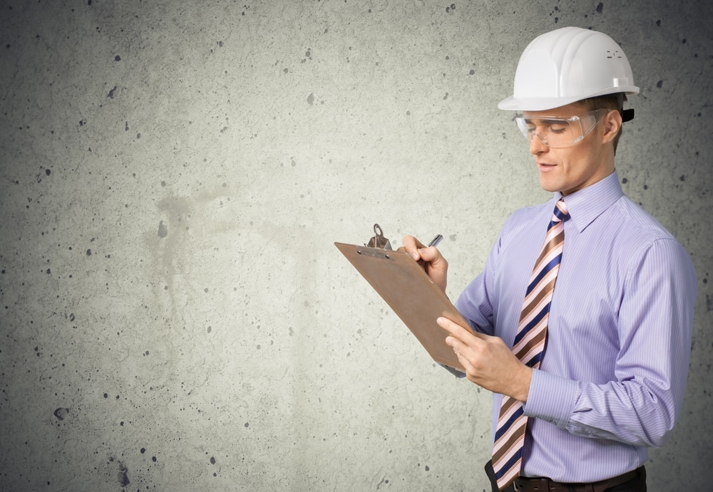 person at construction site with clipboard