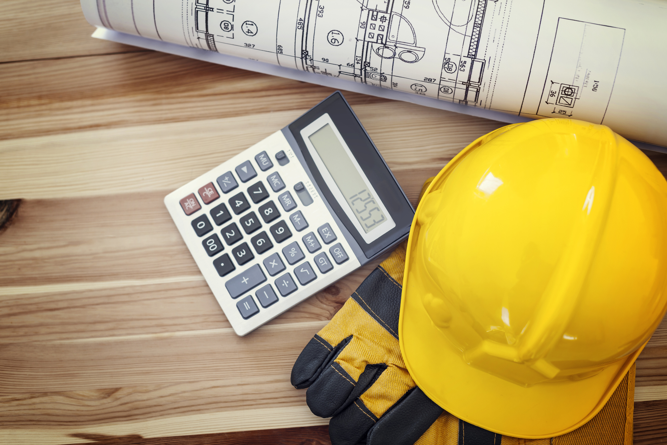 calculator with construction worker hat, gloves, and blue print
