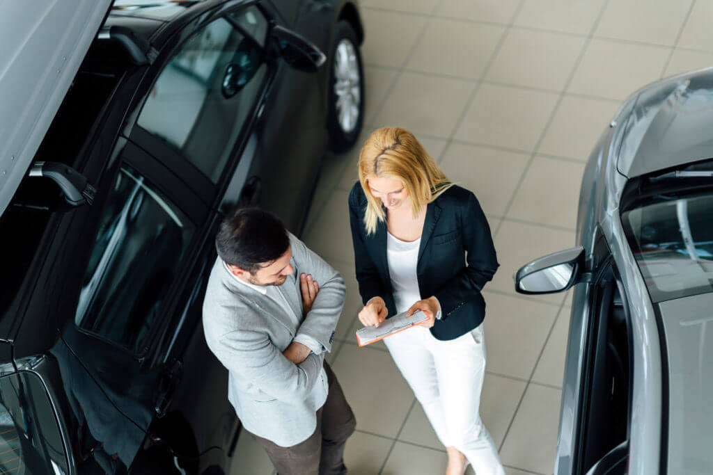 salesperson showing vehicle to customer