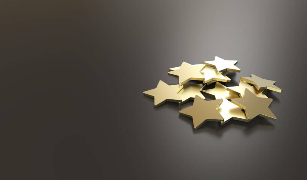 cutout gold stars piled on gray background