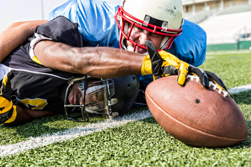 football player making a touchdown while tackled