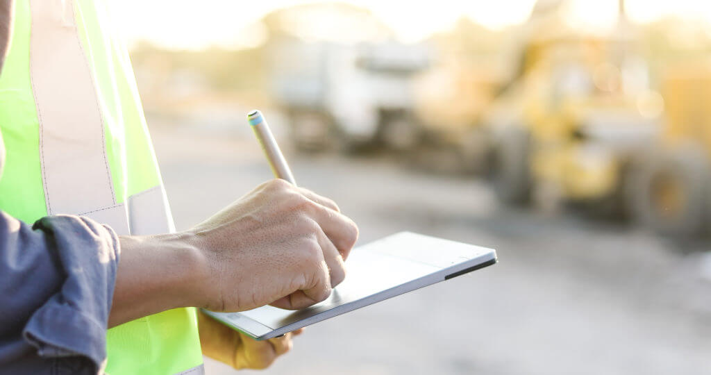 worker writing on tablet