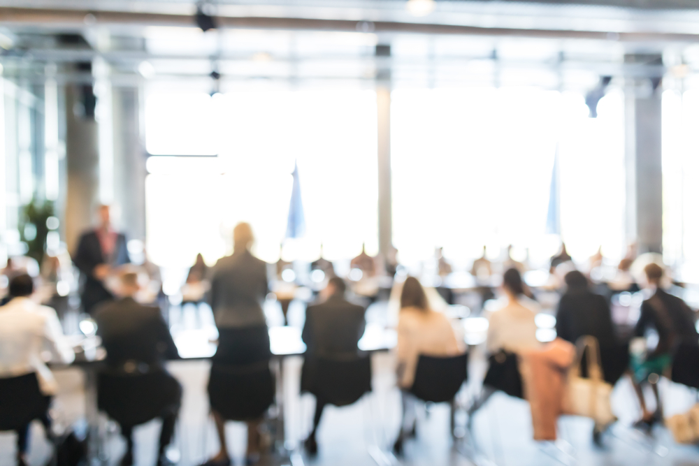 blurry image of office workers in a meeting