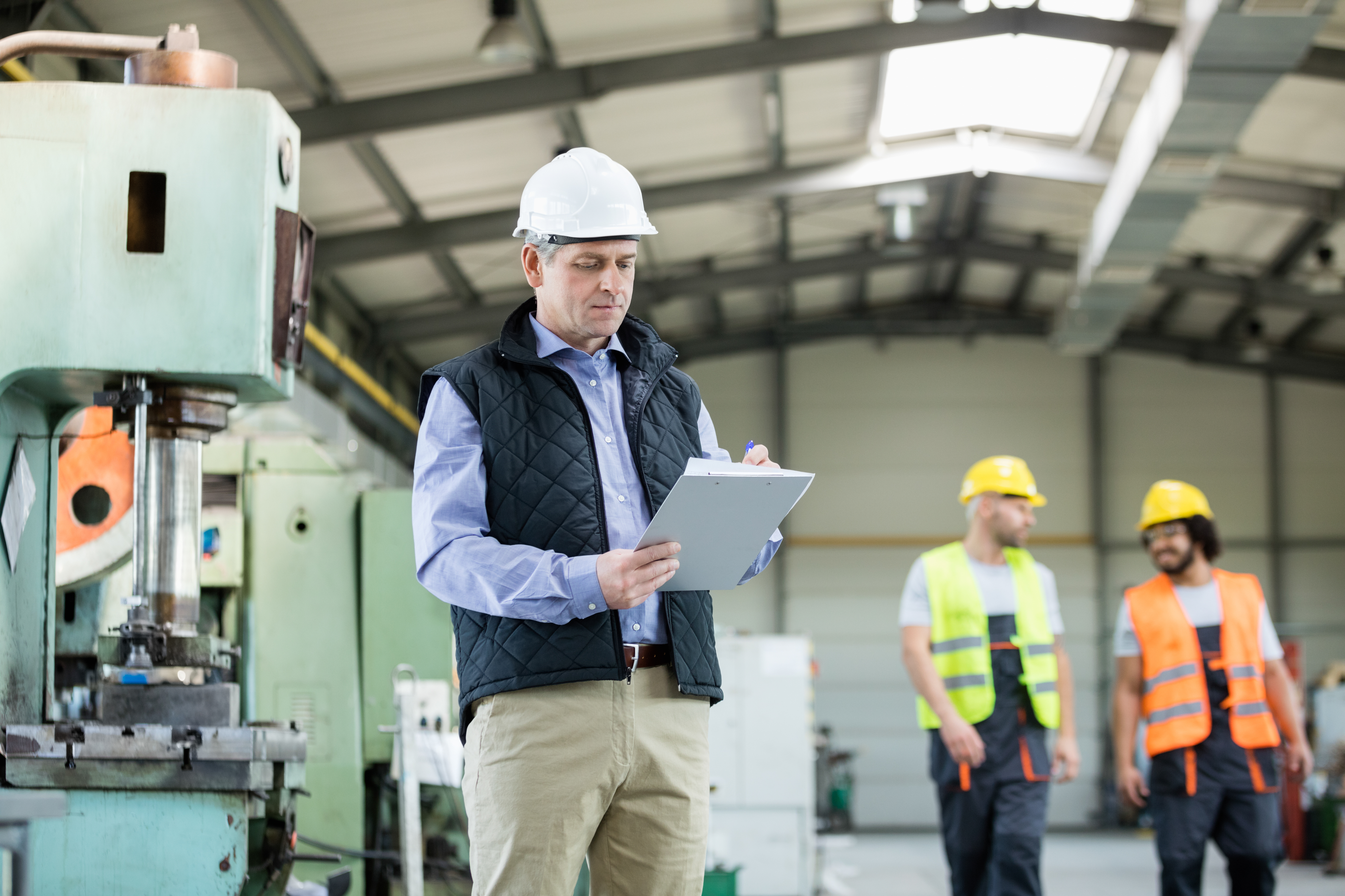 worker in vest and hard hat with clipboard