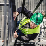 Young male employee climbing ladder in industry