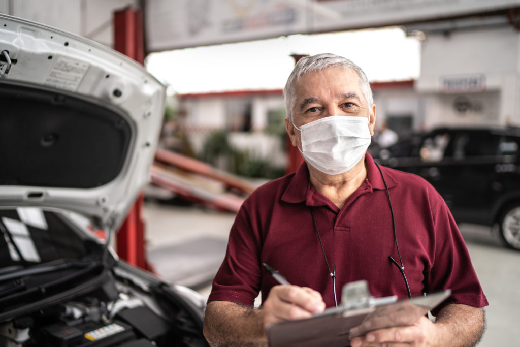 Portrait of auto mechanic senior man with face mask and conducting a safety audit at auto repair shop