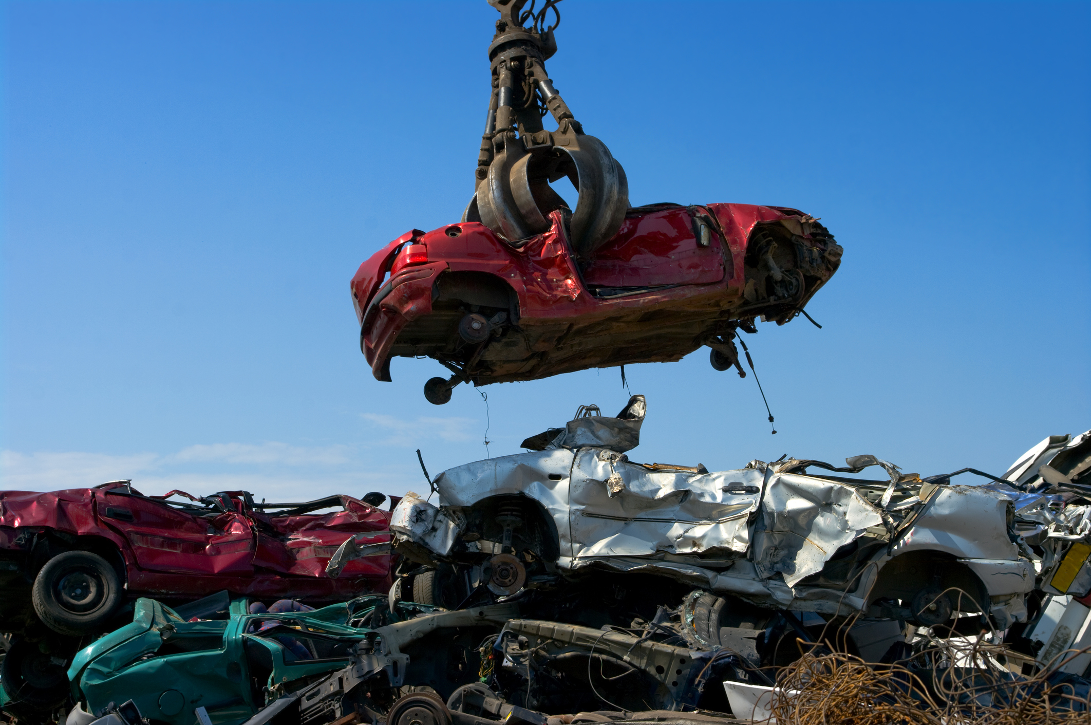 Automobile carried by crane for scrap metal processing images