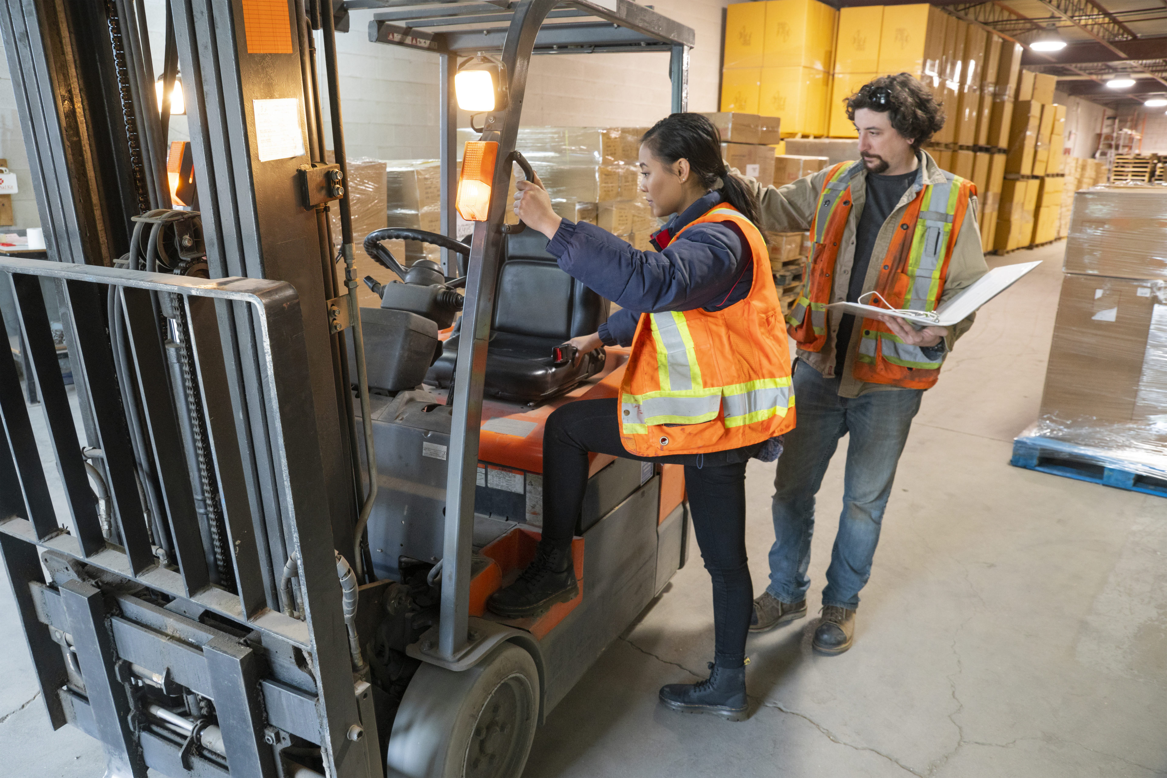 An industrial warehouse workplace safety topic. A safety supervisor or manager training a new employee on forklift safety.