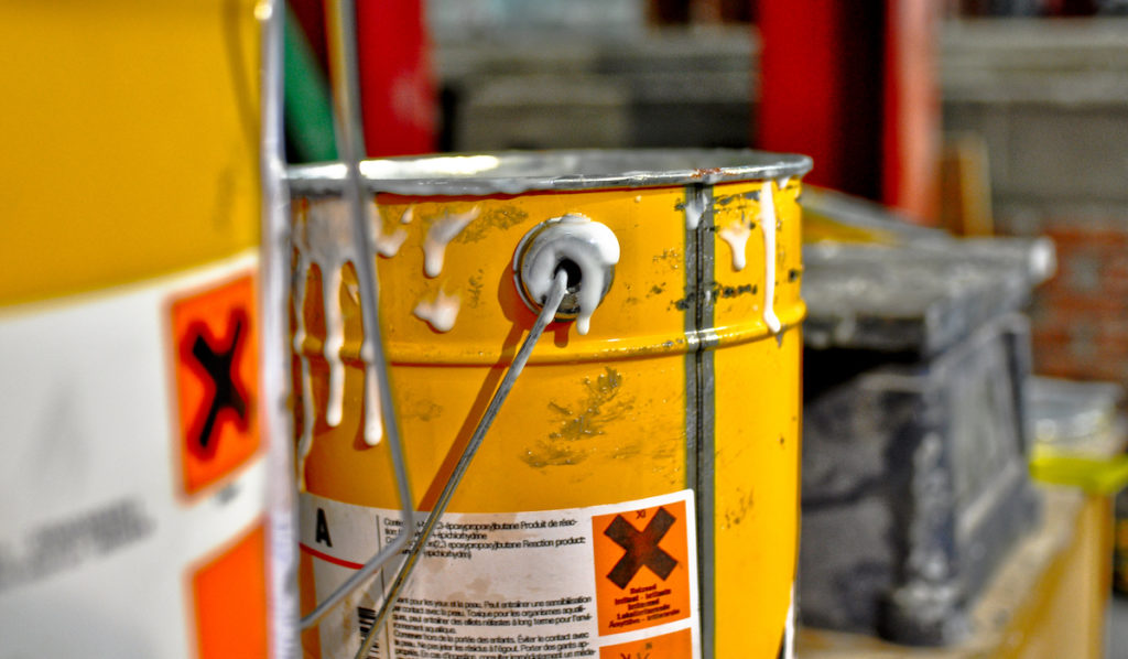 A close-up shot of a bucket dripping with toxic resin an example for businesses who need to focus on chemical spill and leak compliance training