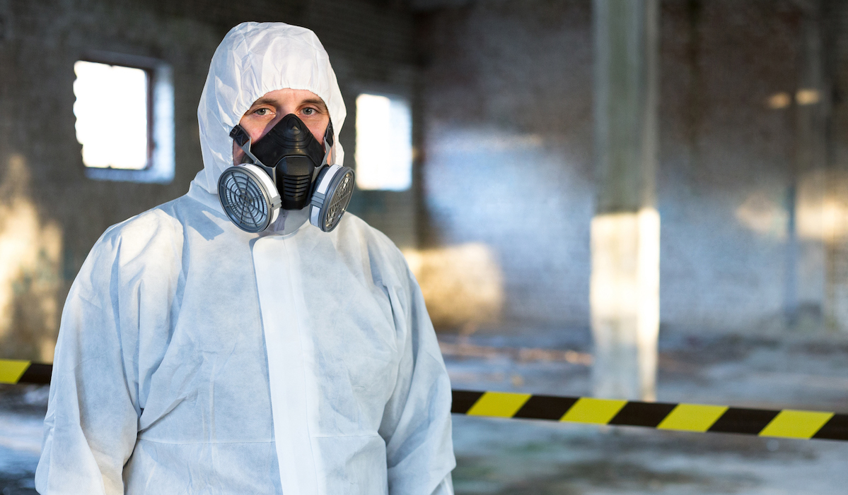 Emergency Respiratory Protection specialist stands inside the building where the accident occurred.