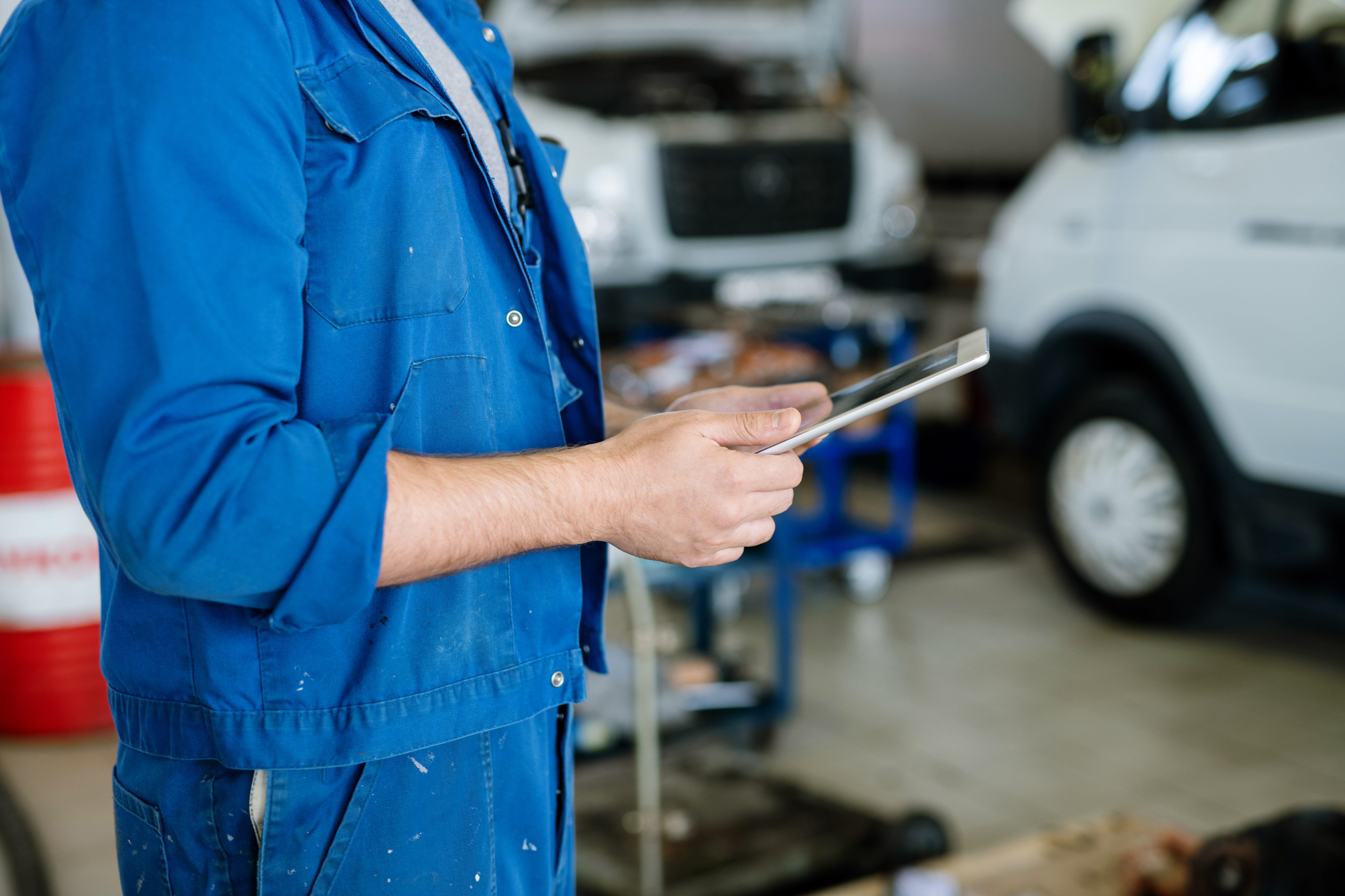 Auto mechanic reviewing ehs software on a tablet
