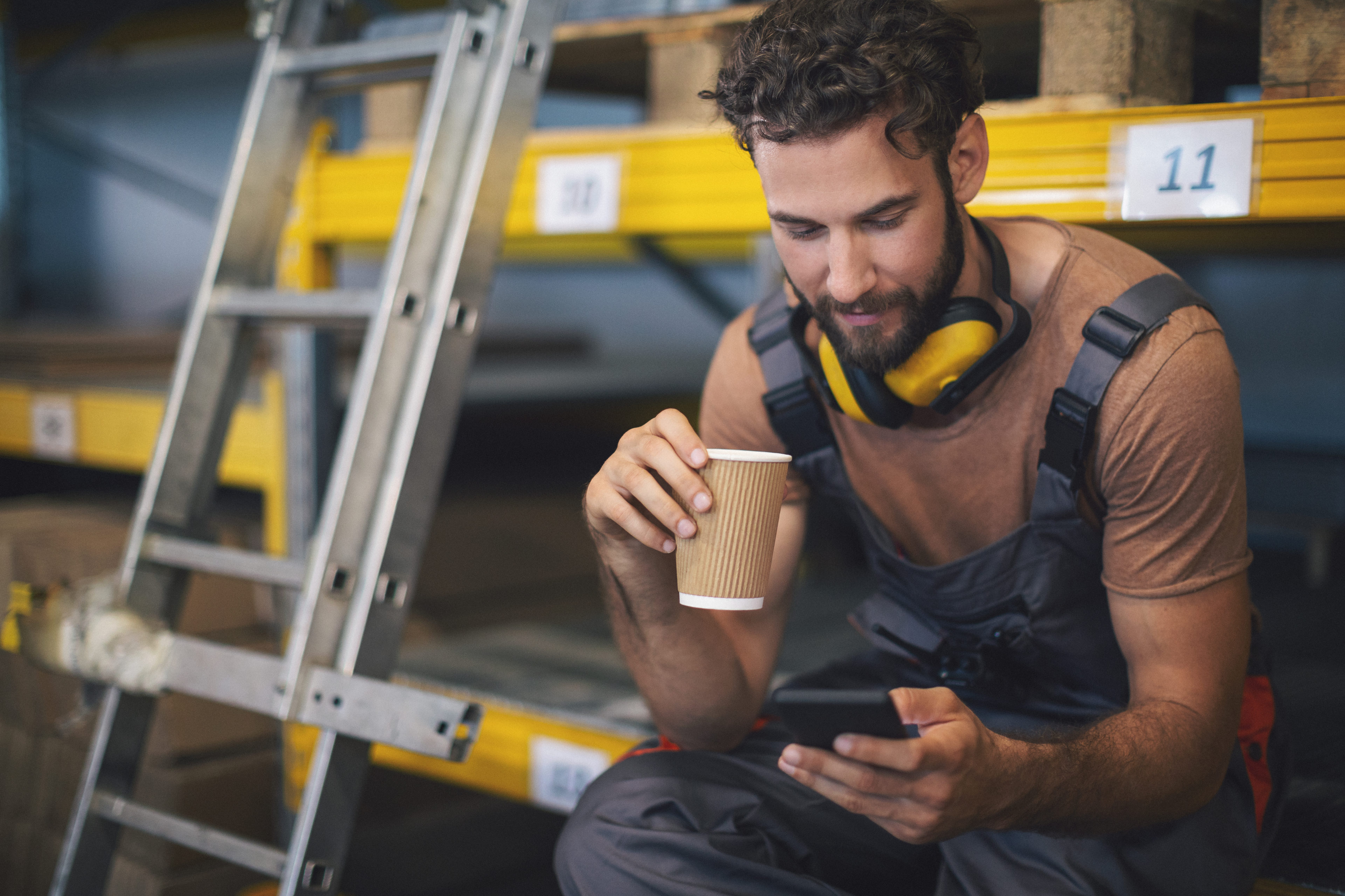 Young worker in the warehouse reviewing mobile training on his phone
